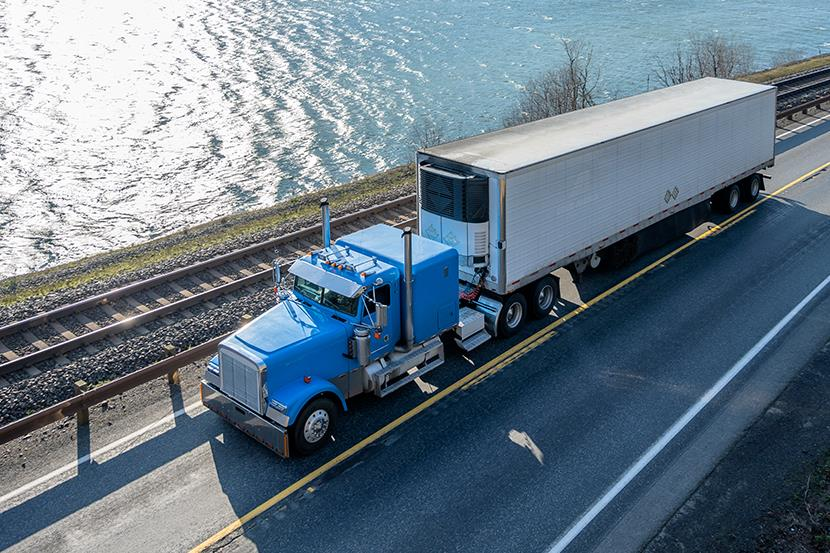 blue big rig semi truck pulling cargo in refrigerated trailer driving on road next to railroad track