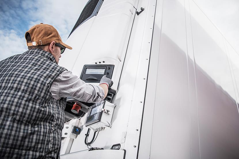 man adjusting temperature controls on refrigerated semi trailer truck