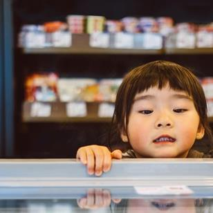 little girl peering over the edge and looking into a freezer chest at a supermarket