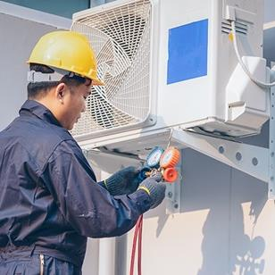 technician holding orange and blue vacuum pump while checking outdoor air conditioning unit