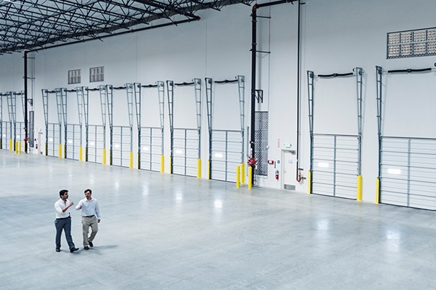 two men walking near loading docks in empty warehouse
