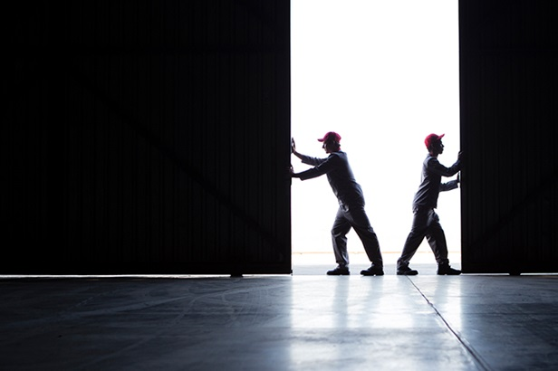 two workers opening up warehouse door