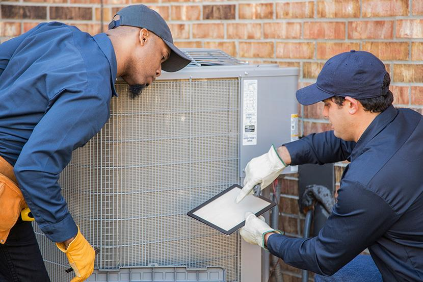 two men net to exterior air conditioning heat pump system one man holding a tablet and the other man