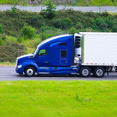 dark blue semi truck with white trailer driving on the road
